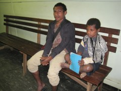 A boy waits with his father to be seen at the hospital.